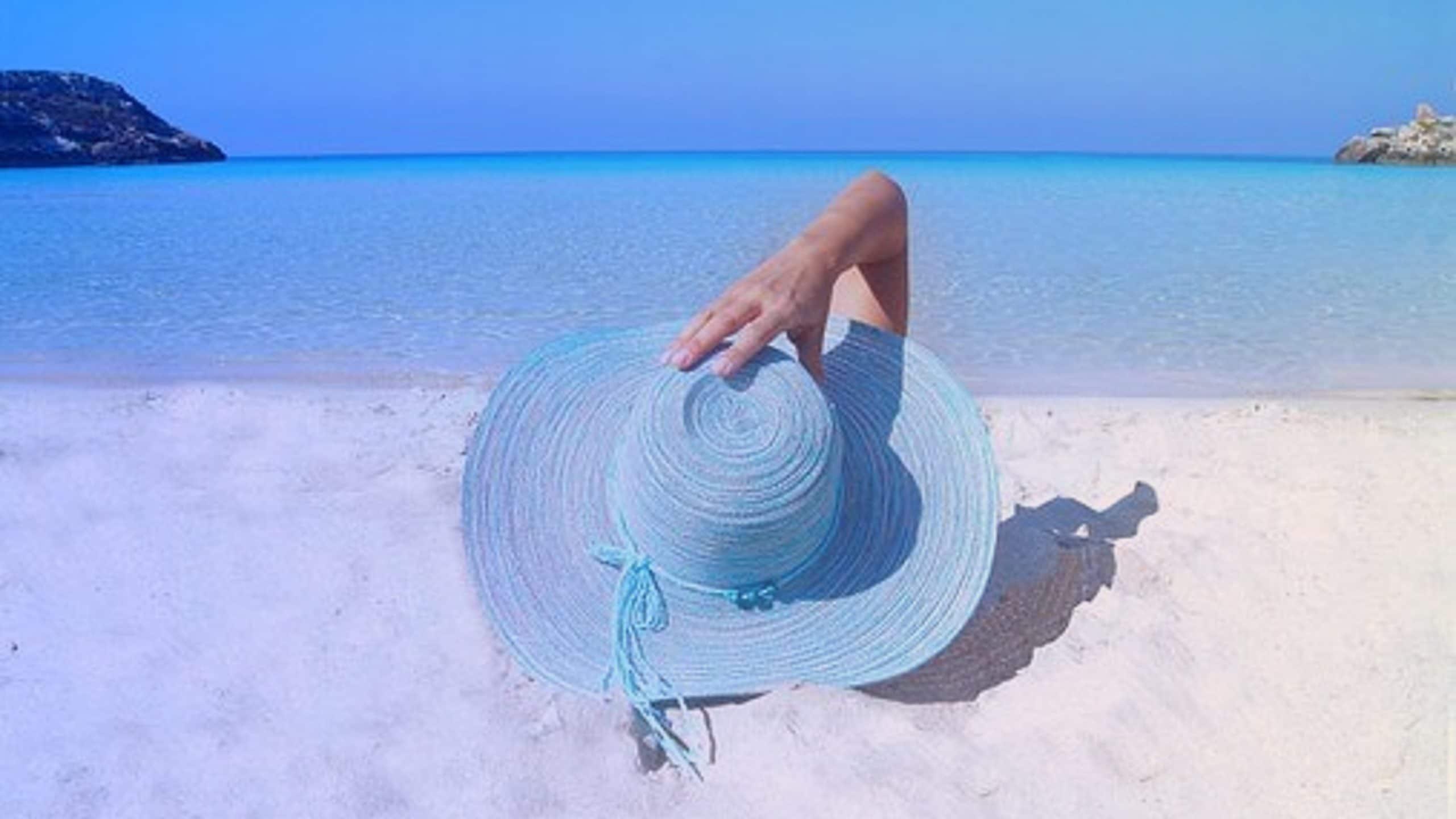 Personne qui bronze devant une mer magnifique pendant son séjour en vacances.