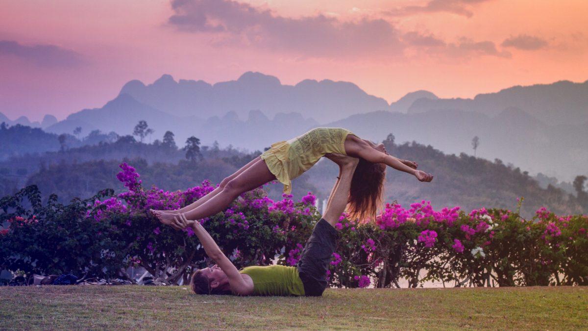 Couple faisant du yoga : faire confiance et s'améliorer